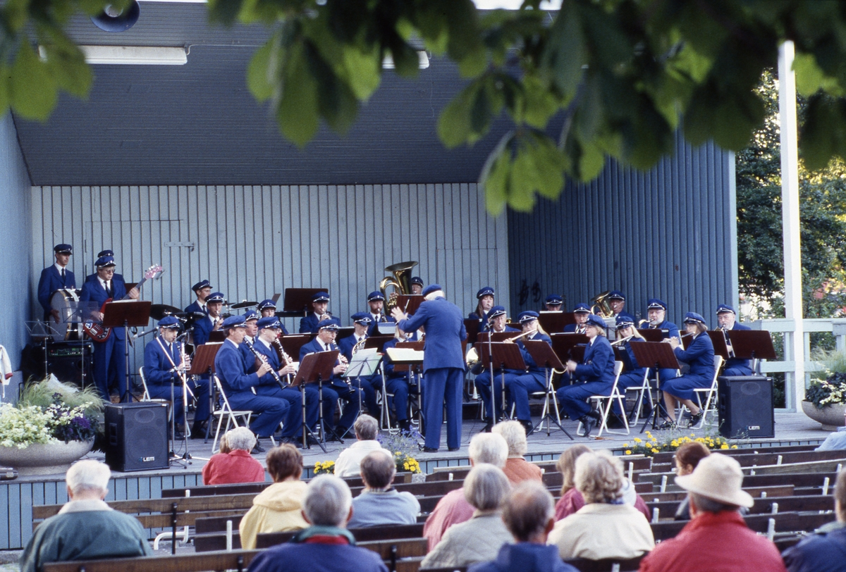 Håkan Harrysson dirigerar Arboga Blåsorkester på sommaravslutning i Ahllöfsparken. Publiken sitter på bänkar framför scenen.
