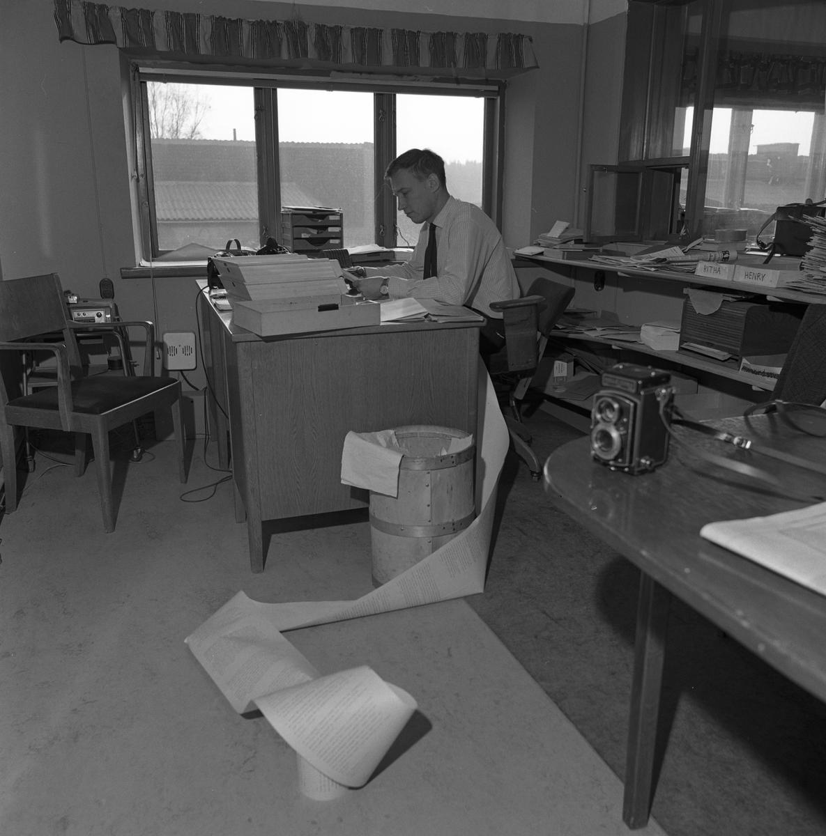 Arboga Tidning, personal och interiör. En man arbetar vid sitt skrivbord. Han har en flera meter lång utskrift, delvis liggande på golvet. I förgrunden står en kamera. Mannen sitter på en kontorsstol på hjul. På andra sidan skrivbordet står en karmstol till besökare. Bakom stolen står en skrivmaskin på ett lågt bord. Skrivbordet står intill fönstret, det syns att kontoret ligger på andra våningen. Bakom mannens rygg finns en låg hylla som är full av papper och tidningar.
