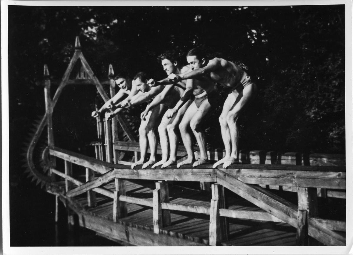 Fyra män står på räcket till kallbadhuset. De ska strax dyka i Arbogaån. Männen är: Olof Viking, Frans Rydberg, Carl Carlberg och Herbert Viking. Baksidan av fotografiet, se: AKF-14466
