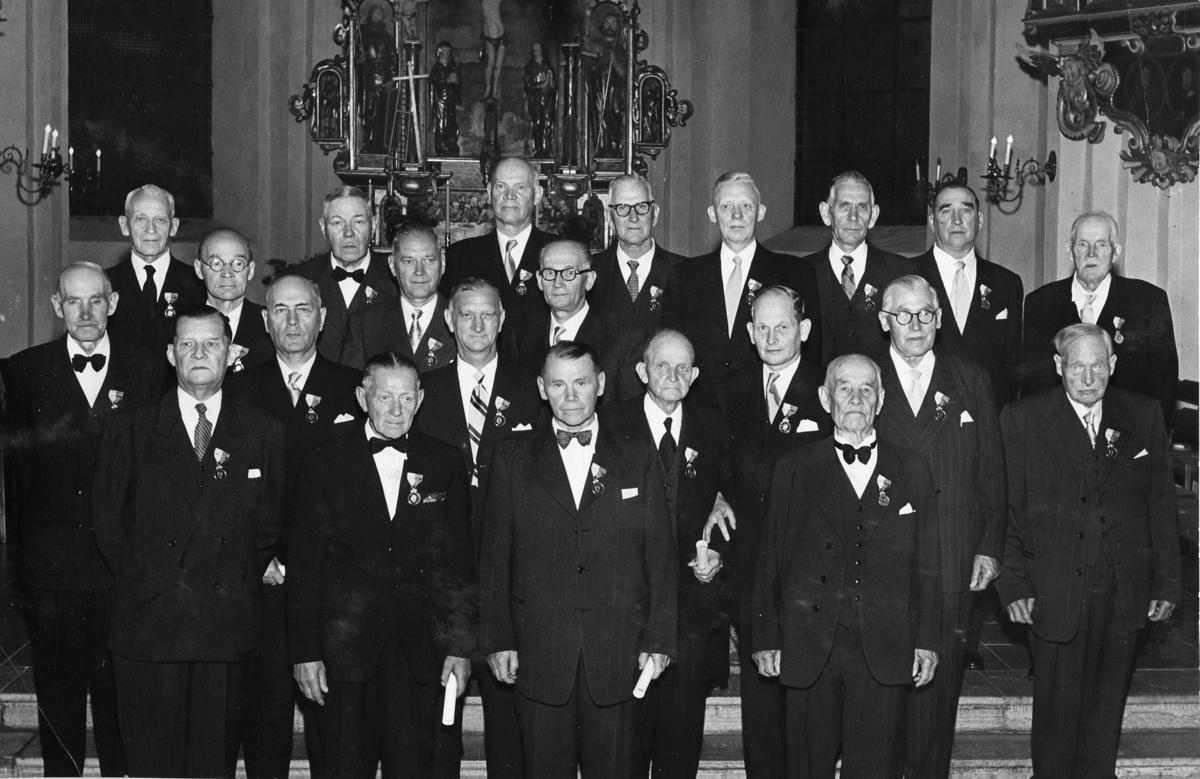 """Medaljer delas ut i samband med Arboga Mekaniska Verkstads 100-årsjubileum. Ceremoni i Heliga Trefaldighetskyrkan. Bakre raden, från vänster: Gunnar Bratt (hyvlare), Ernst Sjöberg (gjutare), Ragnar Bratt (kamrer), Oskar Fehrling (modellsnickare, glasögon), Henry Becker (inköpschef), Gustav Westlund (verkmästare), Uno Fredriksson (elektriker) och Frans Kjellberg (maskinist). Mellanraden, från vänster: Edvard Karlbom (plåtslagare), Verner Liljehult (hyvlare, glasögon), Ture Ekström (förman), Bertil Larsson (kontorist), Johan Karlsson (borrare, """"Borrar-Johan"""", """"Tysta Johan""""), Gustav Brodin (modellsnickare, glasögon), Karl Lindqvist (gjutmästare), Ernst Lindqvist (verkmästare), Birger Zetterberg (svarvare, glasögon) och Emil Wessgren (verktygsarbetare). Främsta raden: Erland Jonsson (förrådsförman), Karl Jonsson (svarvarförman), Henrik Grufman (elektriker) och Karl Blixt (kärnmakare) Namnförteckning på medaljörerna, se bild 14496 25 september 1856 fick AB Arboga Mekaniska Verkstad rättigheter att anlägga järngjuteri och mekanisk verkstad. Verksamheten startade 1858. Meken var först i landet med att installera en elektrisk motor för drift av verktygsmaskiner vid en taktransmission (1887).  Gjuteriet lades ner 1967. Den mekaniska verkstaden lades ner på 1980-talet."""