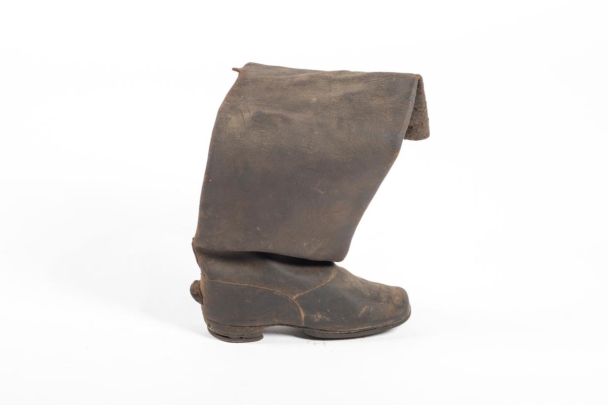 Støvelen er høy og blir videre mot toppen. Skotuppen er rett og skrår oppover. Bak på hælen er det sydd/spikret på en trekantet lærbit som står ut. Under hælen er det naglet på en halvsirkel av metall, lik en liten hestesko. Det er et snitt bak på støvelhalsen. Opp fra støvelens innside stikker det to brede lærremmer, muligens til å trekke på seg støvlene med. Materialet er mykt og kraftig.