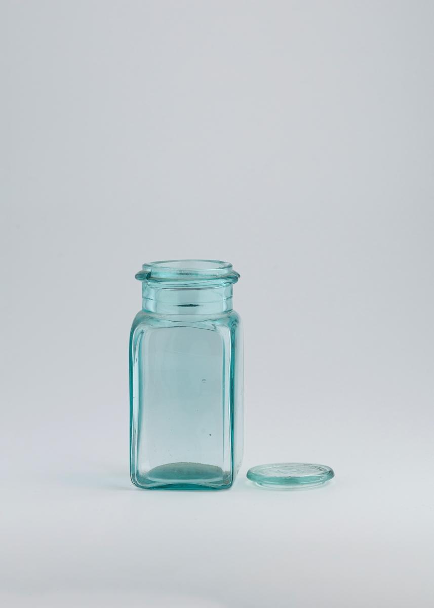Firkantet glasskrukke med avrundede kanter. På toppen av glasskrukken er det en rund åpning med rand rund. Oppå krukken ligger et flatt lite lokk i glass som sitter løst.