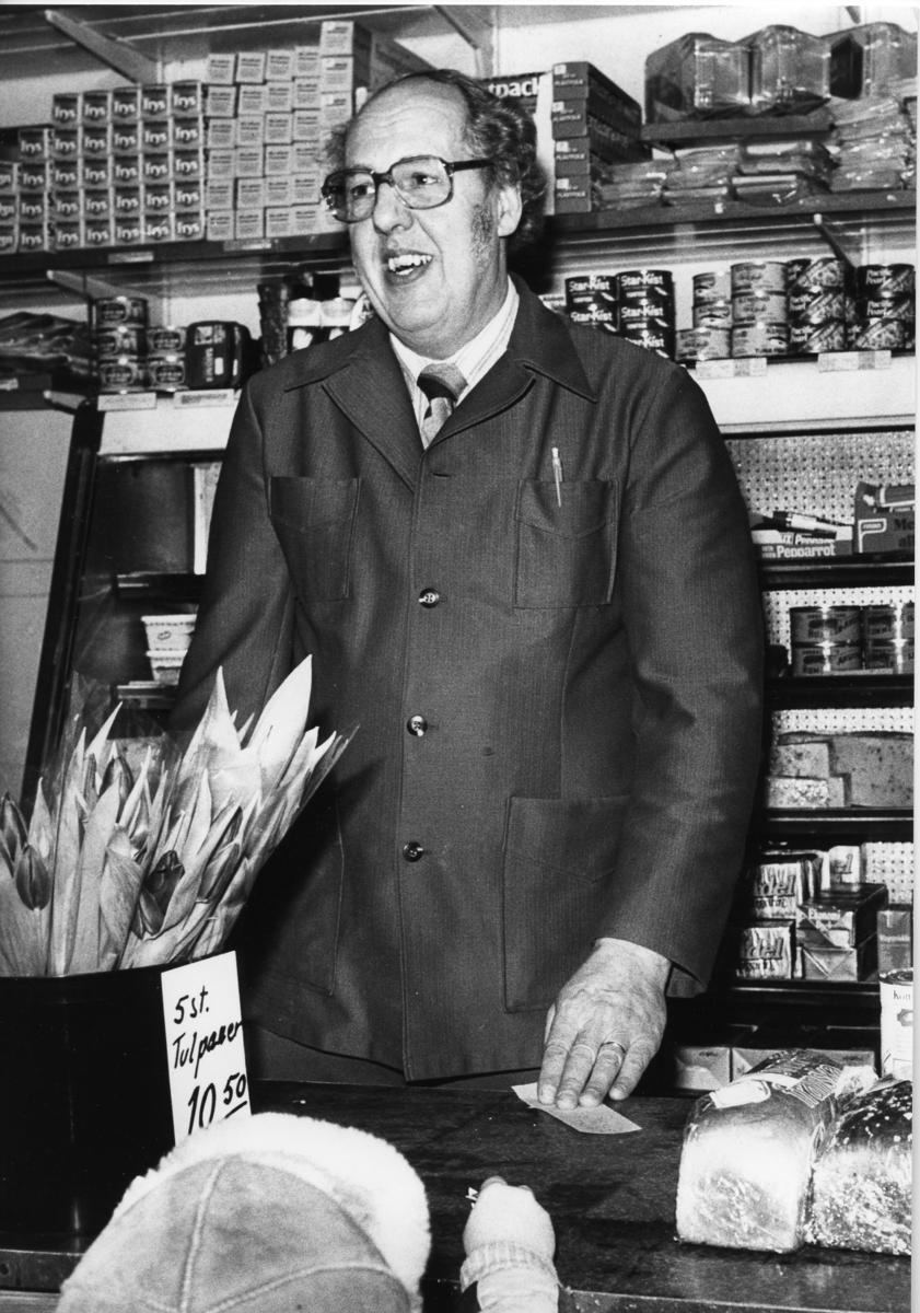 Bengt Adolfsson i butiken. Ett litet barn har kommit för att handla. På disken står en hink med tulpanbuketter och två limpor skymtar. På hyllorna, bakom Bengt, finns diverse specerier.
