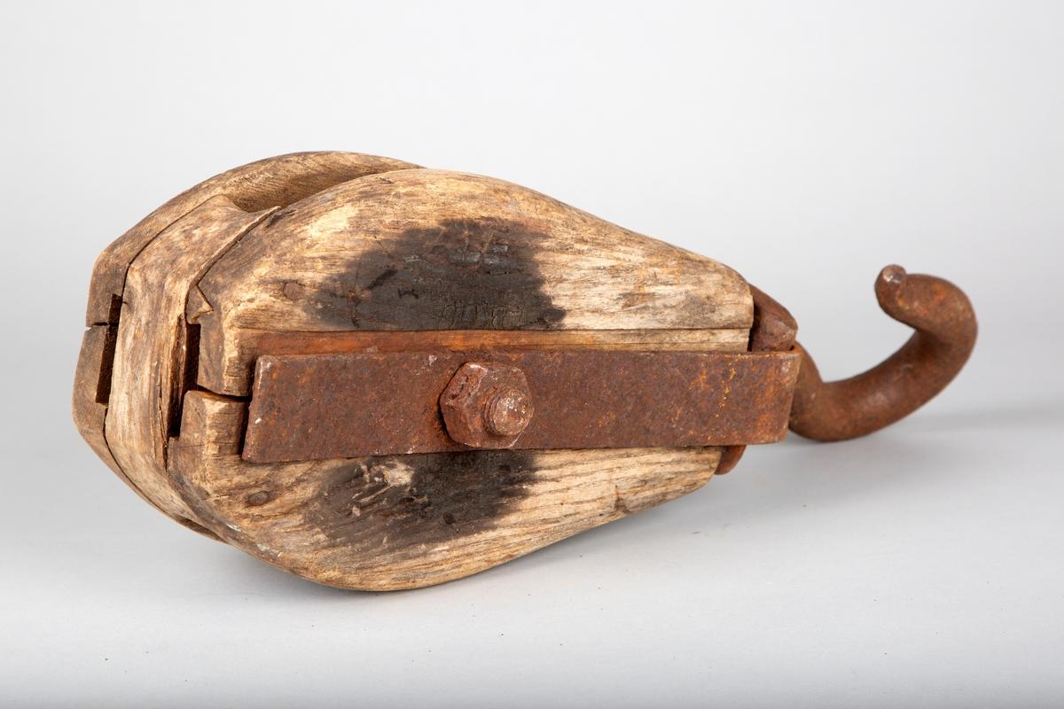 Blokk med krok. Løfteanordning for bruk ombord i fiskebåt. Denne har trolig vært brukt ombord i M/S Rusken, som var en av båtene Grøntvedtbrødrene eide.  Merking på ene langside, den andre langsiden har et svidd parti.