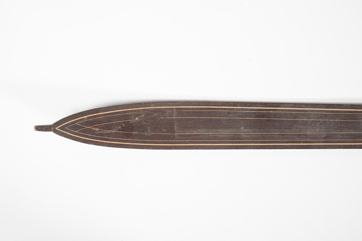 Ski med jevn bredde, svinger litt inn på midten. På midten av skien er det en forhøyning med påspikret plate som forsterkning. Bindingen består av lærremmer over tær og vrist, og bak hælen. Remmene er festet til en bøyd jernplate, som er festet i en spalte i skien, under forsterkningen. Skien er rett bak og spiss foran. Skien krummer oppover foran, og har en liten tapp ytterst. Under skien er det en renne i midten. Det er utskåret striper langs oversiden av skien som dekorasjon. Det er festet litt tau i bindingen.