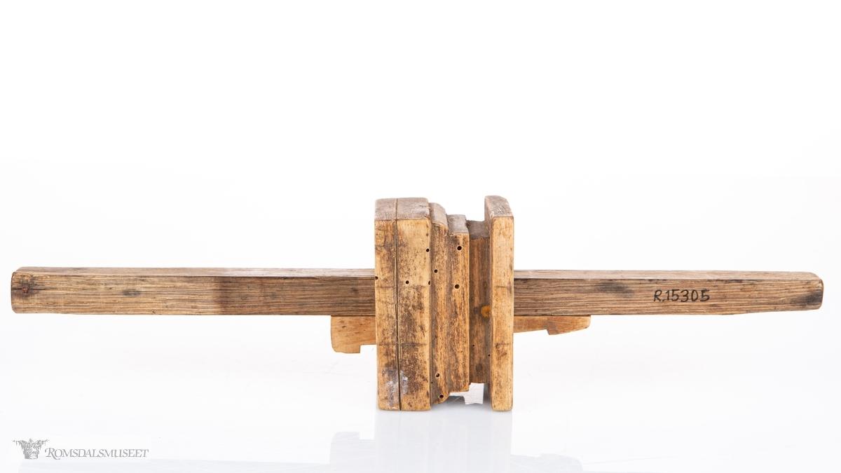 Rektangulær kloss med rektangulære, regulerbare pinne og kile i midten. Rissenål i enden av den lengste armen.
