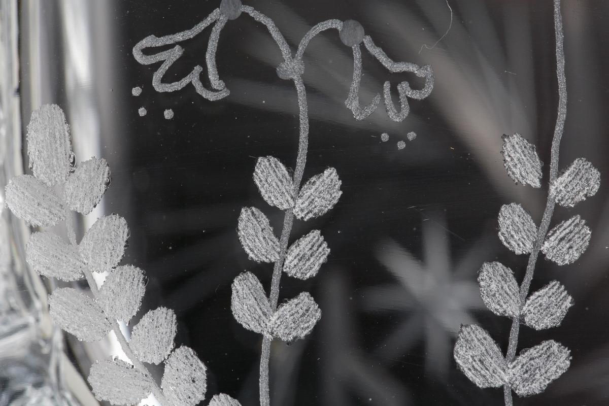 """Kraftig skål med grov relief längs sidorna. Fram och baksidan plana och försedda med slip- och gravyrmönster. Ena sidan tre st graverade linnéor och på andra sidan snedställda skär i en ring runt en mindre stjärna. Etikett: Silver med svart text """"SH // Handslipat glas // Eneryda Sweden"""""""