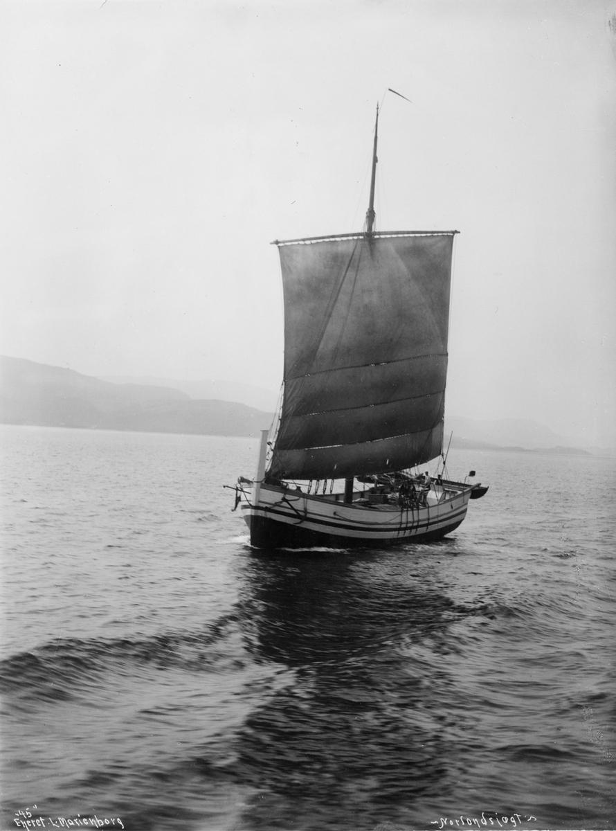 """Motivet viser en nordlandsjekt for fulle seil i kystlandskap. To menn ombord, lettbåt henger i akterspeilet. Fotografiet er merket """"45"""" Eneret L- Marienborg -Nordlandsjægt-."""