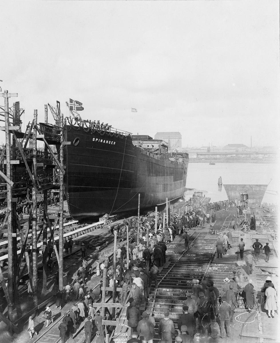 Motivet viser MT SPINANGER (bygget i 1927) under stabelavløpning ved Schiechau i Gdansk. Norsk flagg og rederiflagget til Westfal-Larsen. Verftsarbeidere og andre frammøtte i fremre del av motivet. Samme motiv som BSJ 2018-002-00025.