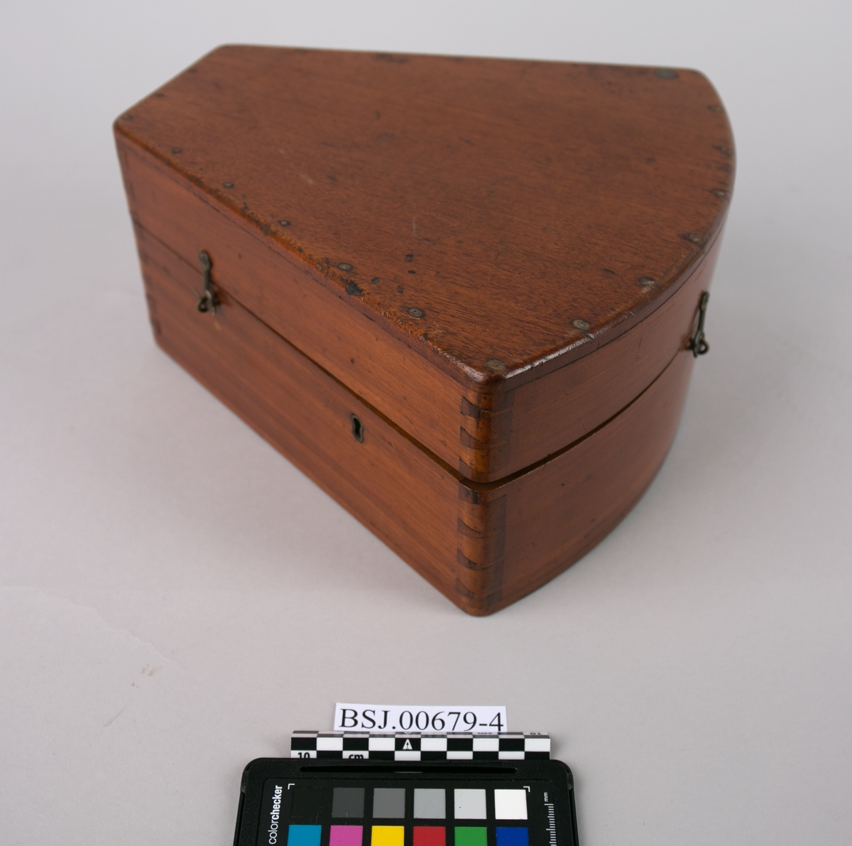Kasse. Transportkasse til sekstant og løse deler til instrumentet. Trekantet kasse med buet form i den butte delen. Nøkkel mangler.