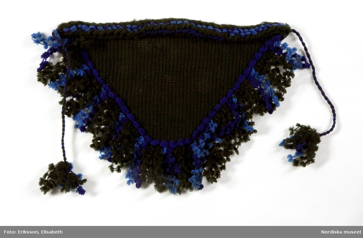 """Trekantig huvudbonad av svart ullgarn i tunisisk virkning, i framkant en vulst av svart och blått ullgarn och på övriga två sidor frans av långa ullgarnsöglor med """"kläppar"""" av svart och blått garn i två nyanser. Knyts under hakan med svart yllesnodd avslutad i ändarna med kläpptofsar.  Bil. = """"Lurka , införd av den för några år sedan avlidna bruframman fru Vixner, Användes ej mera"""" (1914) Kallas ibland även pingellurska med tanke på kläppfransen (pinglor). Bars mest av äldre kvinnor.  Berit Eldvik okt.2005"""
