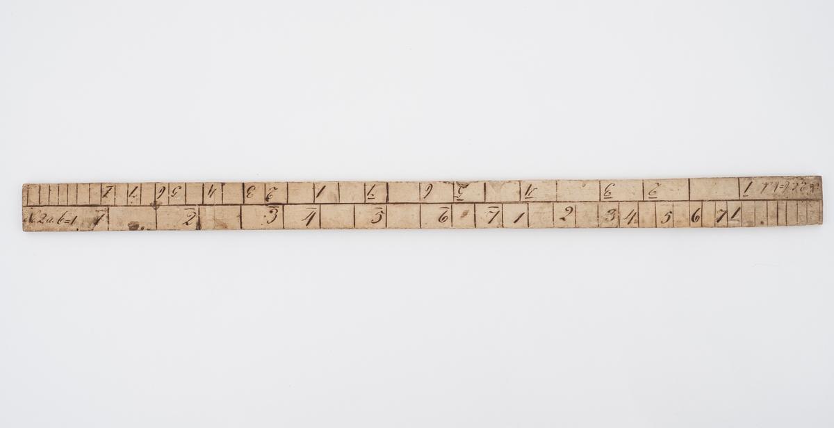 Rektangulær målestokk. Treverket er dekket med et tynt lag papir. med tall og bokstaver skrevet på. Papiret er sannsynligvis limt på. Målestokken har to rekker med tall på hver side. De samme tallene er brukt på begge sider, men oppsettet er ikke likt.