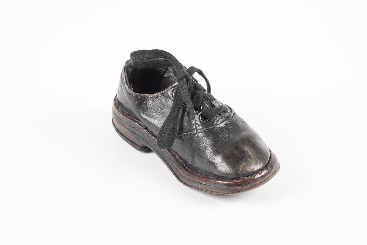 Et randsydd barnesko (venstre sko) av lær. Skoen har snøring med flate lisser. Maljene er av metall. Sålen er av lær og er forsterket med spiker på hælen og ved tuppen på undersiden.
