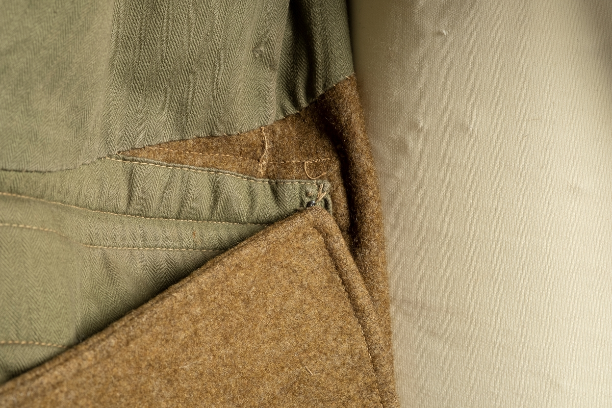 En grønn dobbelspent ullfrakk med to lommer i front. Lommene har klaffer. Ermene har oppbrettet mansjetter. På venstre bryst er på påsydd et norsk flagg. Kragen kan brettes opp og kneppes igjen. På hver skulder er det en knapp og en hempe. Knappene er av plast. Frakken er foret med bomull. På lommeposene på innsiden av fraken er det metallhektere for å kunne hekta opp endene på frakken slik at blir kortere foran. Bak er det en splitt.