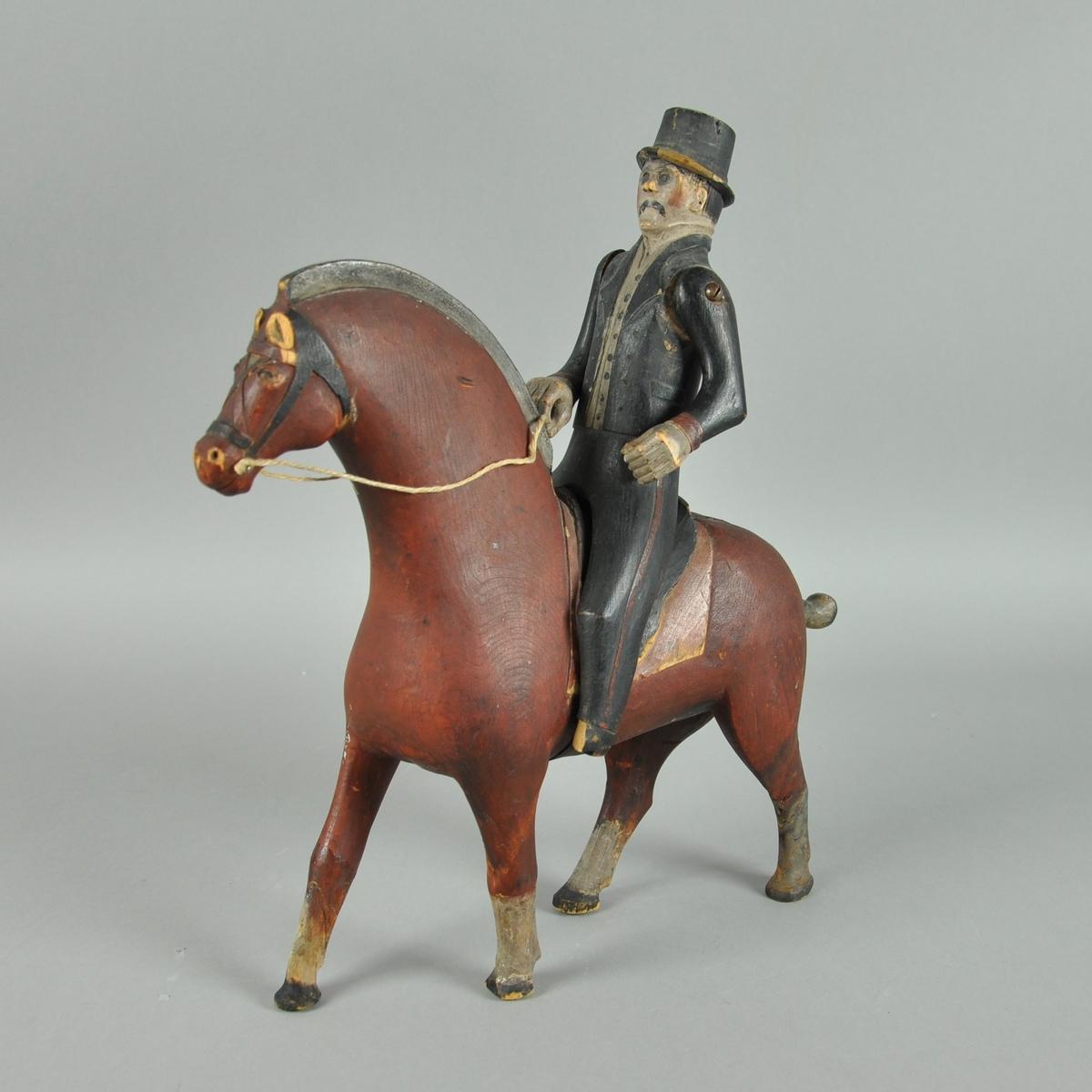 Lekehest med rytter. Hesten er skåret ut av ett trestykke og er malt brun, med svart mal. Rytteren har armer som er skrudd fast og har malte svart klær og hatt.  (Den ene armen er løs, skruen sitter ikke fast).