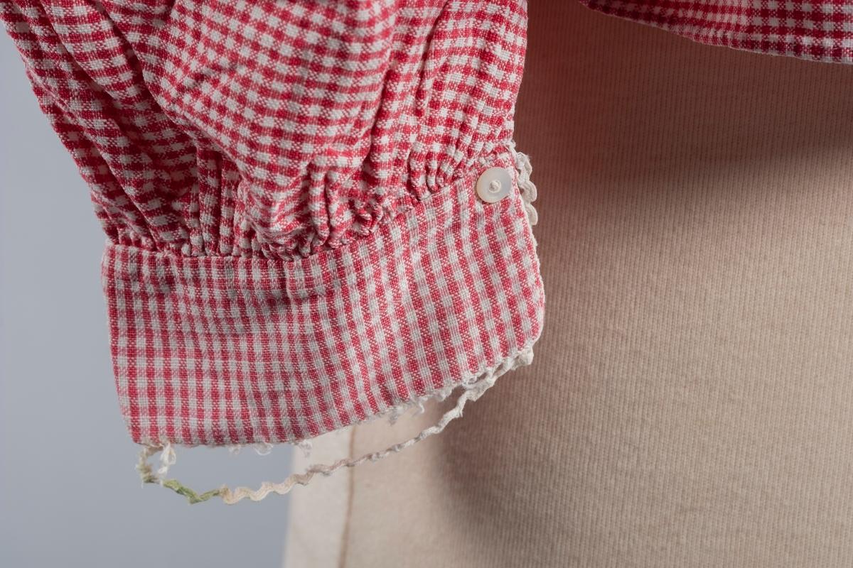Rød og hvit rutete nattrøye i bomull med puff- og ballongermer. Den har blondekanter på kragen og mansjettene. På mansjettene er det perlemorsknapper. Trøyen har en høy krage. Det er sydd folder bak ved kragen og øverst på ermene. Trøyen har åpning i front og lukkes med én plastknapp i kragen.