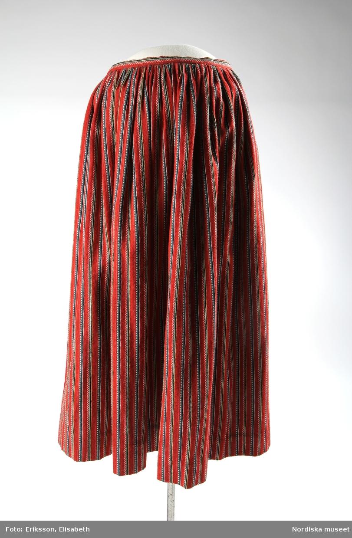 Kjol av halvylle med varp av brunt bomullsgarn och täckande inslag i tuskaft av entrådigt ullgarn, smala ränder i blått, vitt, gröngult, svart och ljusare rött mot mörkt röd botten. Tätt rynkad mot 2 cm bred midjelinning av tyget. I sidan ett 17,5 cm långt sprund som knäpps med en sleif av linningen med två svarta tryckknappar på var sida om hake och hyska, sprundets fåll är skodd med ett vinrött tyg, under sprundet en ficka med fickpåse af grått bomullstyg. Utmed linningen på insidan ett svart band. Kjolens fåll skodd med ett 1,5 cm brett ripsvävt bomullsband i rött, blått och vitt.  Till kjolen användes moderna resårhängslen för att kjolen, som var tung och lite för stor, skulle sitta uppe ordentligt i midjan, se hängslen [NM.0334223]  Jfr kjol NM.0000432 från Skedevi sn, Finspånga läns hd, ÖG, insamlad 1873.  /Marianne Larsson 2019-03-25