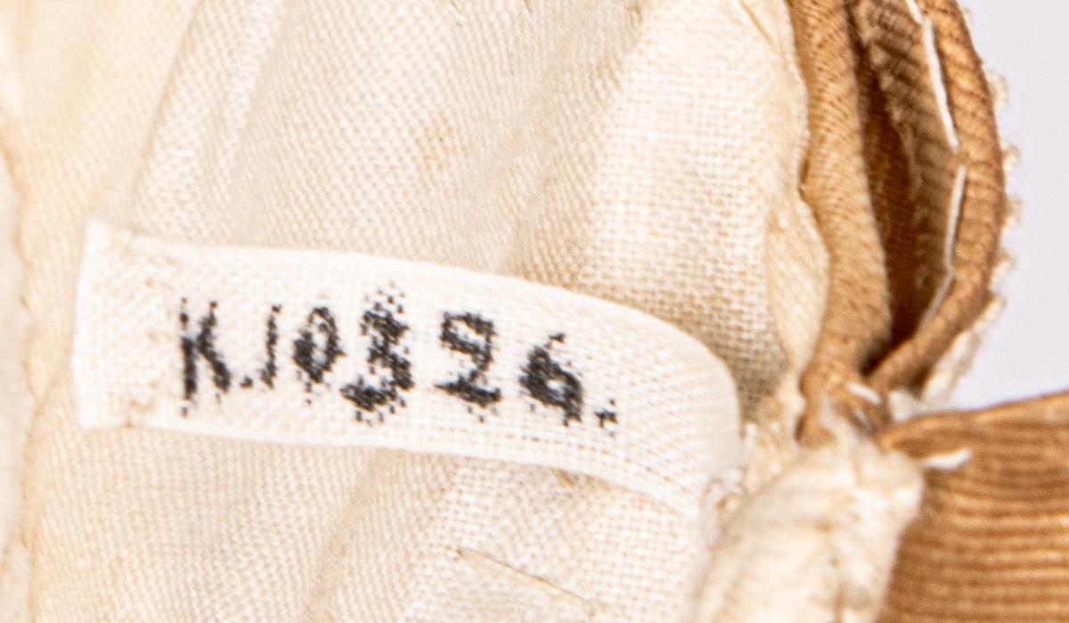 Flickmössa av beige rips, broderad med vita smala ganser, veckad rysch. Längd 32cm, bredd 22cm.