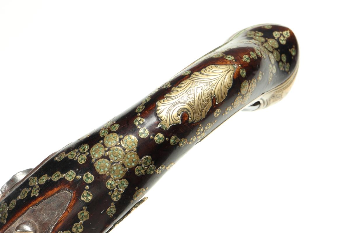 """Slaglåspistol av 1600-talstyp med koniskt utsvängd pipmynning omändrad från flintlås under 1800-talet. Den är försedd med dekorerad helstock bestående av inläggningar i mässing och emalj i form av blomformade ornament. Kolvkappan av mässing har en heltäckande gravyr som avslutas med en ansiktsliknande kolvknapp. Runt kolvknappen löper en bokstavsfris som visar """"NANNAN"""". Låset och pipan av stål har bladliknande gravyr. Sidoblecket består av en gjuten/graverad mässingsplåt. Tumplåten av mässing har ett växtornament, samt att varbygeln och avtryckaren är tillverkade av graverad mässing. I laddstocksrännans bakre del finns en dekorerad spetsrörka. Även det främre rörkoret i mässing har enklare utsmyckning. Det främre pipbeslaget är av ben. Pipan är slätborrad med en innerdiameter på 17 mm.  Inskrivet i huvudkatalog 1939"""