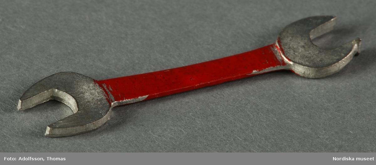 11 st verktyg för en snickare: a-b) u-nycklar (2 st), c-d) filar (2 st), e) skiftnyckel, f) skruvmejsel, g) hammare, h) handborr, i) yxa, j) hyvel och k) såg. Den sistnämna har ett brunt trähandtag medan de övriga är helt i metall med påmålat rött eller grönt handtag. Hör till dockskåpsinredningen i källarens snickarverkstad i dockskåp NM.0331721+.