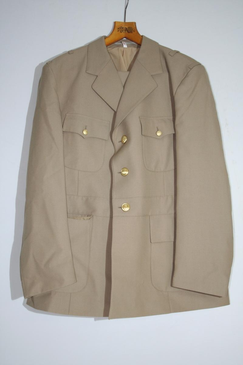 Beige jakke og bukse. Jakka har metallknapper, men ikke distinksjoner.