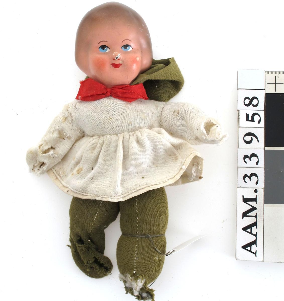 Tøydukke med støpt hode i plast.  Ståltrådskjellet i armene. Grønne bukser og hvit kjole, rød sløyfe i halsen.