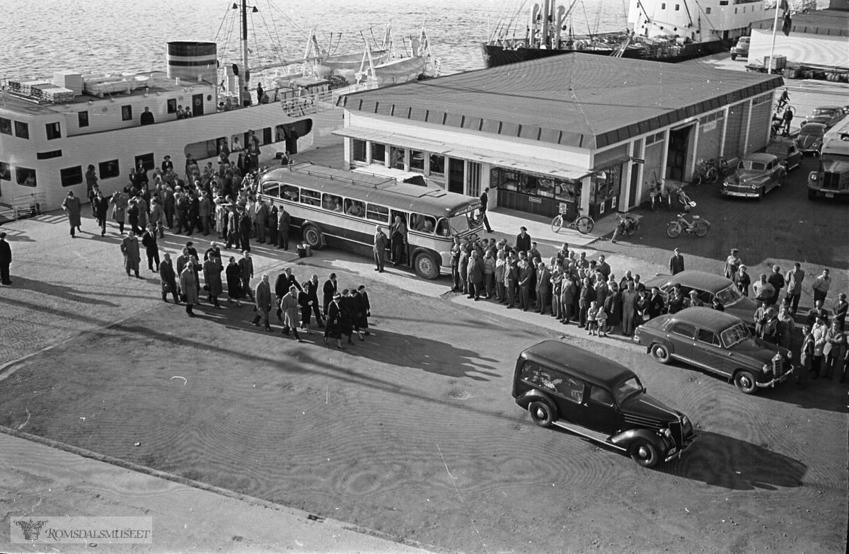 """""""September 1958"""".""""Oksviks gravferd"""".Fra begravelsen til Olav Oksvik f.07.05.1887 d.16.09.1958..Båten som ligger til kai er M/S Romsdal, som gikk i rute Åndalsnes-Molde-Ålesund i tidsrommet 1950-1962. Den ble solgt i 1962..Bussen på bildet er sannsynligvis T-8685 Scania-Vabis, 1953-modell, med karosseri fra Bussbygg, Hovdenakken. Bussen tilhørte Aarø Automobilselskap (Auto) og den var lakkert i gult og mørk blå. Aarø Auto hadde ruter Molde-Kristiansund over Gjemnes, og ruta startet og avsluttet ved Storkaia i Molde, der det var korrespondanse med båter til Åndalsnes og Ålesund. .Begravelsesbilen er en Ford V8 1936 med registreringsnummer T-2167...På høyre side av bygningen en Dodge eller Chrysler personbil 1946-48-modell og til høyre for den utsnitt av en Scania-Vabis semitrailer."""