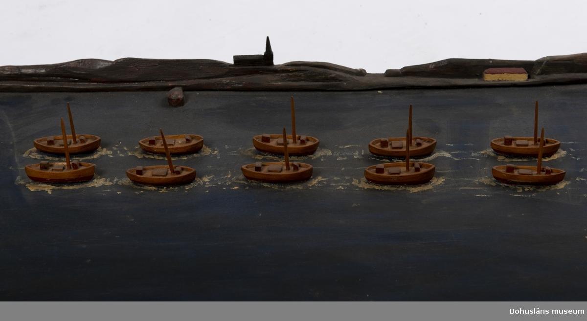 """Rektangulär träplatta med fjorton båtar, två och två, i en rad. I fonden är det en siluett av ett kustlandskap med berg, ett hus och en kyrka. Text framtill på plattan: """"SKARPSILLSFLOTTAN PÅ VÄG GENOM GULLMARSFJORDEN"""". En större båt saknas. Master saknas på vissa av båtarna.  Ur handskrivna katalogen 1957-1958: Skarpsillfångstflottan Modeller på platta. Plattans mått: 116 x 42. Föremålen hela. Från kapten Olssons saml., Fiskebäckskil.  För ytterligare information om förvärvet, se UM005087."""