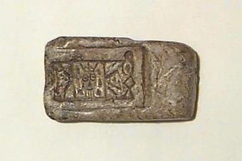 På ena bredsidan streckfigurer (bl.a. ett ansikte med en krona), på den motsatta sidan en hemisfärisk urgröpning. Även en oval urgröpning på ena smalsidan. I huvudliggaren upptagen som gjutform för rektangulärt spänne.