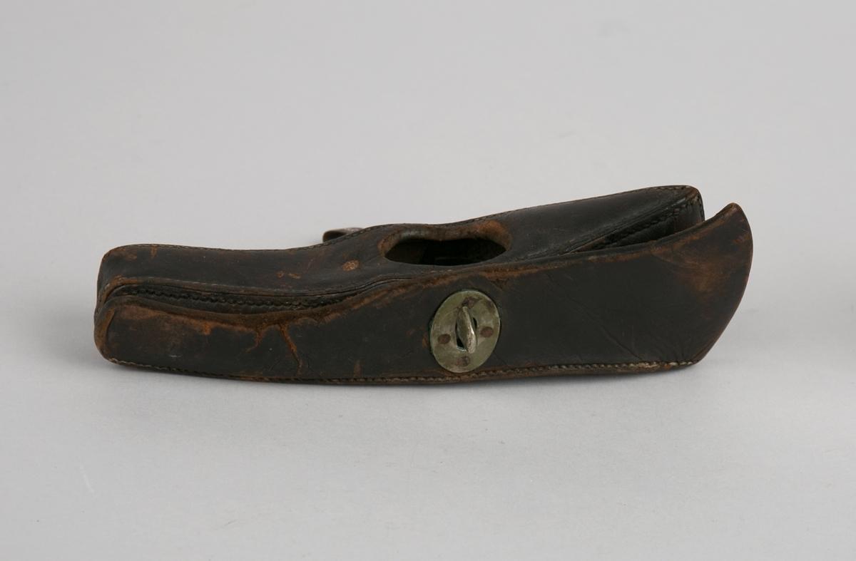 Futteral til brannøks. Futteralet er sydd i skinn og har form som øksehode. Lukkes med klaff med hull og knapp. Hempe av jern til oppheng i belte.