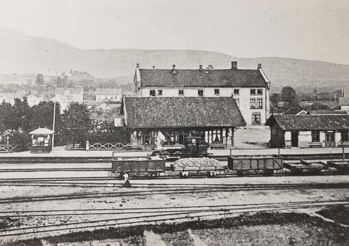 """Lier stasjon. Nærmest stasjonsbygningen damplokomotiv type VI nr 3 METIS eller nr. 4 HYGEIA. Lokomotivet ble benyttet som assistanselok fra Lier opp til Spikkestad og ble omtalt som """"Merra i åsen"""". I forgrunnen godsvogner litra L, M og K."""