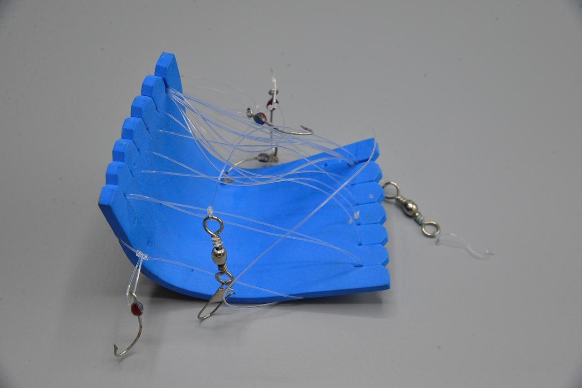 Fiskesnøre med seks kroker viklet rundt en plate i skumgummi.
