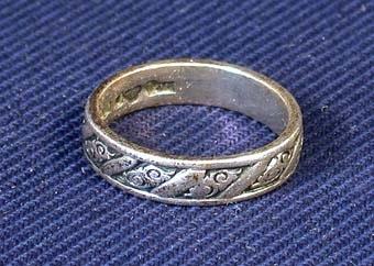 Kamratring av silver med snedställda band med bladliknande mönster emellan runt om hela ringen. Silverstämpel inuti.