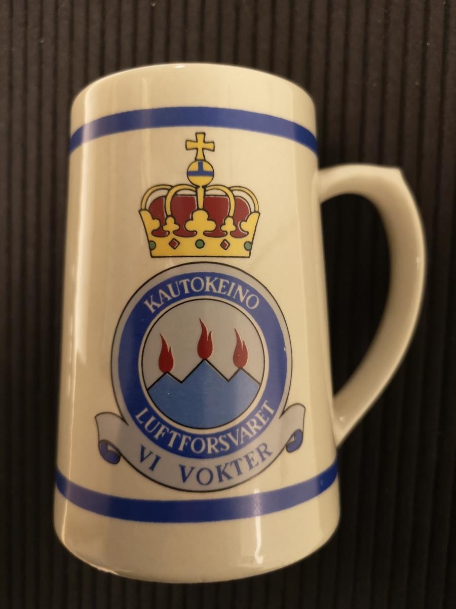 """Luftforsvarets emblem på baksiden. 3 varder og tekst """"Vi Vokter"""" på forsiden."""