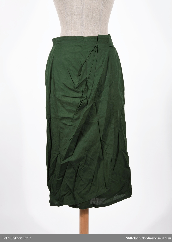 Grønt skjørt som festes med knapp og glidelås. Spesielt utformet snitt foran, som et foldeskjørt - overlappende åpent snitt fra linning og ned.