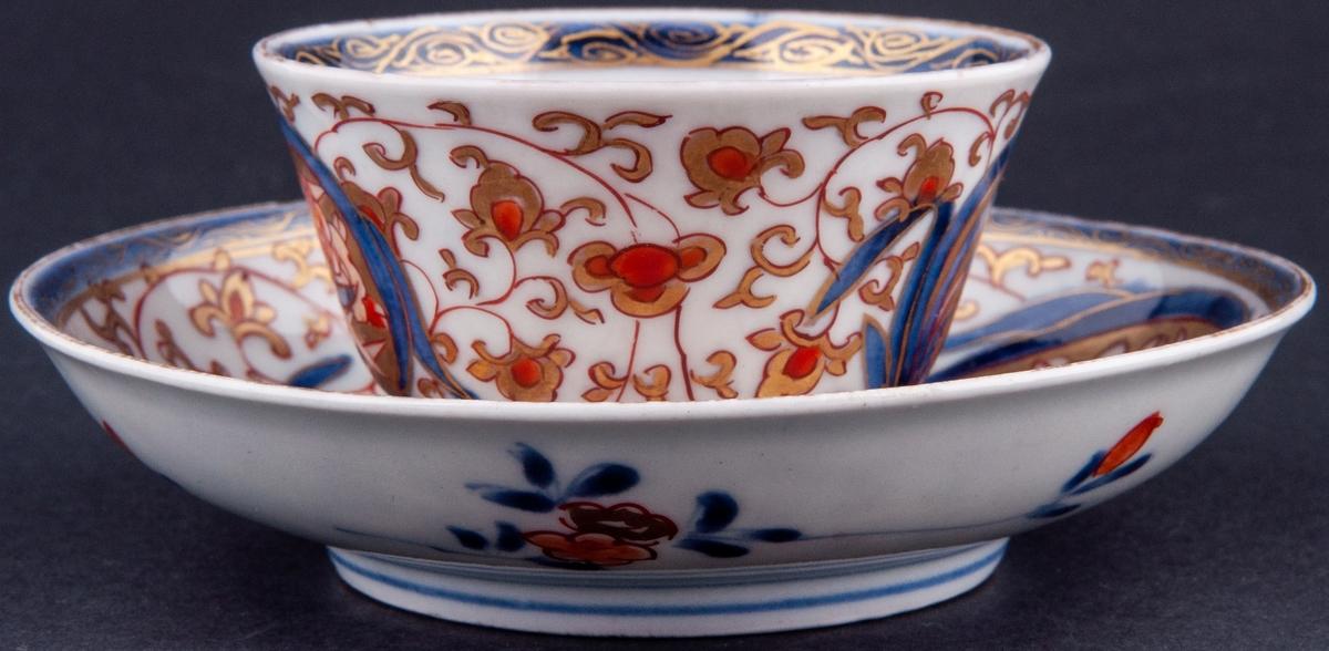 Kopp och fat, kopp utan öra. Vit glasyr med överglasyrmålning i blått, orange och guld. Utan stämpel, kompaniporslin.