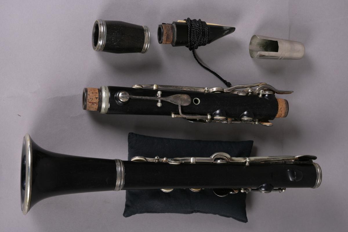 Klarinett i mørkt tre i fem deler. Overstykke, understykke, klokkstykke, pære og munnstykke. Klaffer i messing.