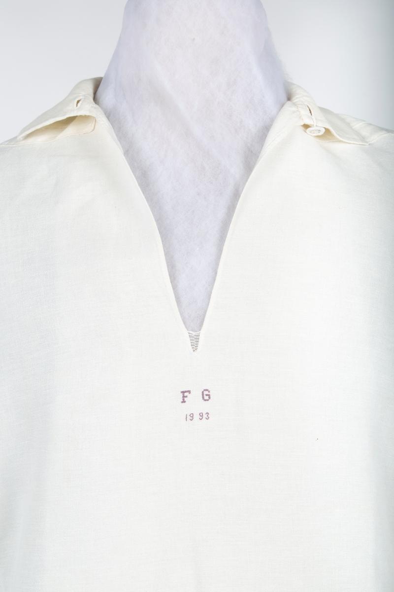 """Skjorte til Follobunad. Høy krage og lang halssplitt. Stikninger på hals- og håndlinninger og på skulderstykkene. To knapper og sprette i halsåpningen. Håndsydde stikninger på halskrage, mansjetter og skulderstykker. Holdes sammen i halsen av to trådknapper; trådknapp og hempe på mansjetten. Under halsåpningen brodert med små korssting FG som står for """"FolloGubben""""  Skjorten er sydd av ??.  Orginalen til skjorta kommer fra Hokholt på Nesodden. Skjorta til bunaden er en nøyaktig kopi av orginalen"""