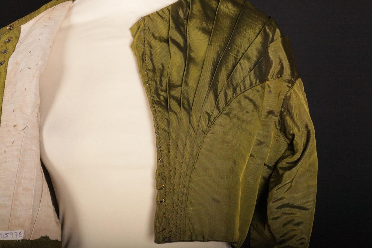 Kjoleliv sydd av grønn silke. Sydd for hånd - håndsøm. Lukkes med hemper og hekter.