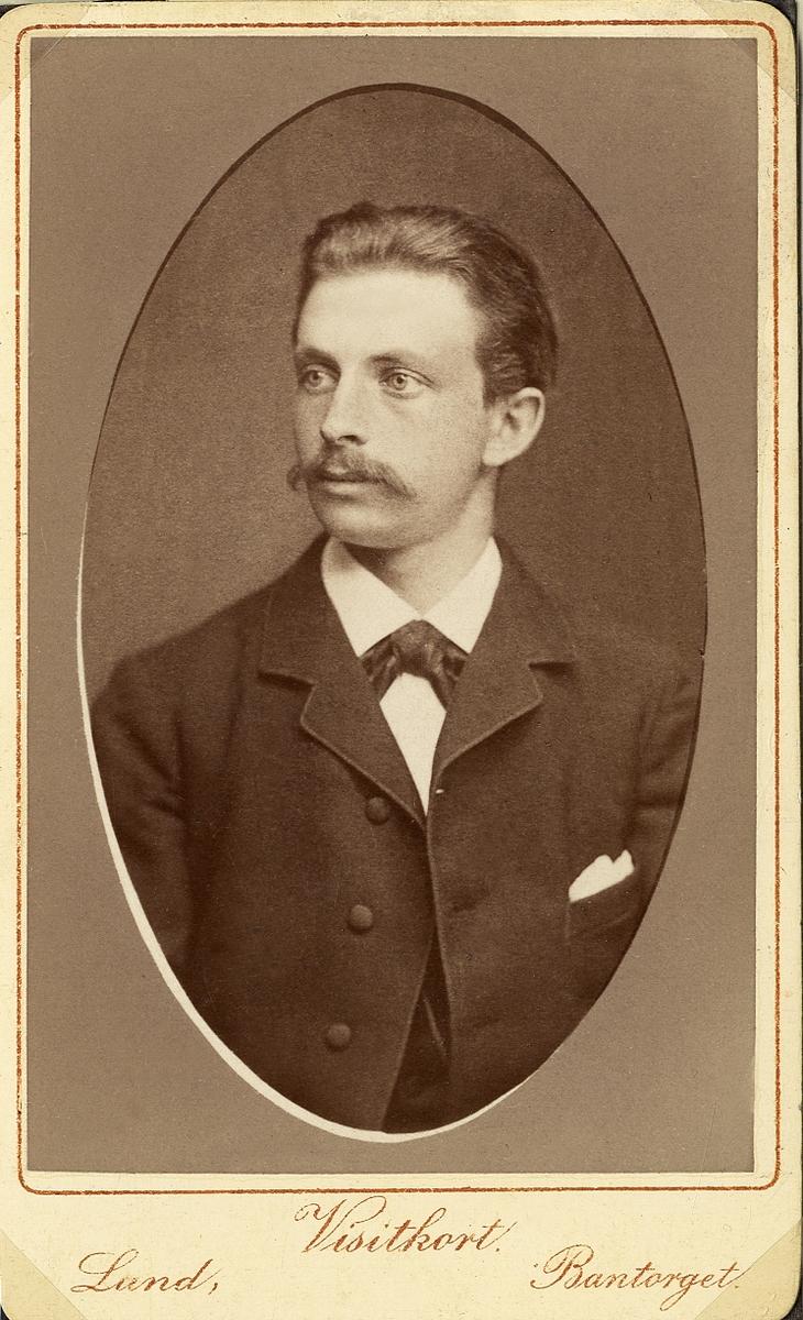 Porträttfoto av en ung man med mustascher, klädd i mörk kavajkostym med fluga.  Bröstbild, halvprofil. Ateljéfoto.