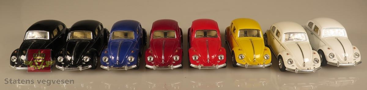 Samling av flere modellbiler. Alle er av samme produsent og produsert i lik tidslinje. 2 biler er svarte, 2 biler er hvite, 1 bil er gul, 1 bil er blå og 2 biler er røde. Alle er laget av metall og har en skala på 1:32