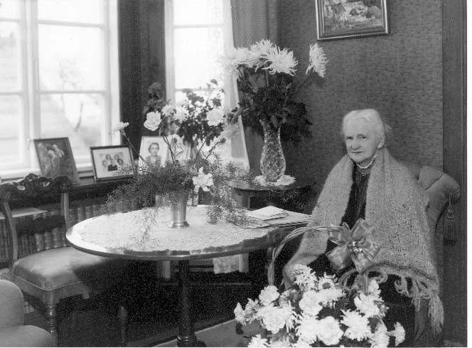 Porträtt av Albertina Kellner i samband med hennes 90-årsdag. En vithårig dam som sitter i en fåtölj i sitt hem med en sjal över axlarna, omgiven av blomsterbuketter.