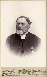 Foto av en äldre skäggig man med glasögon, klädd i prästrock
