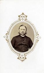 Foto av en man med polisonger, klädd i prästrock och prästkr