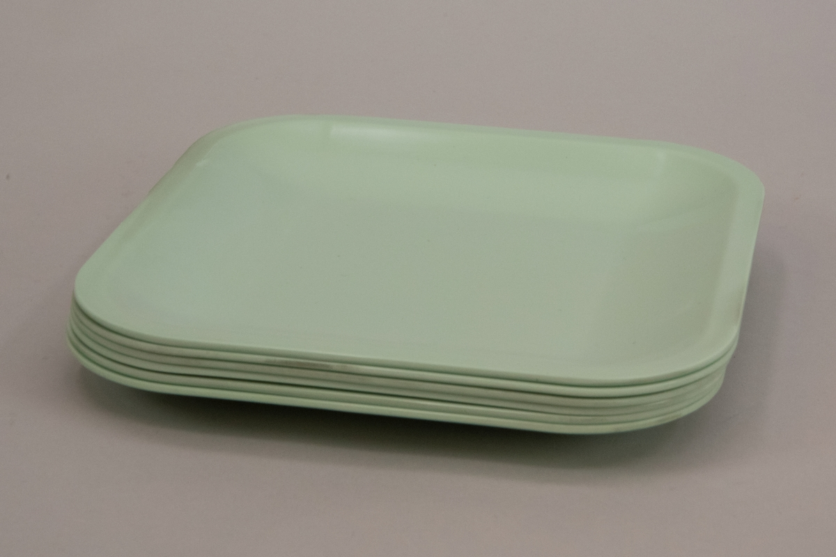 Sex stycken tallrikar av ljusgrön mepalplast, fyrkantiga med rundade hörn. Plan spegel och uppvikta kanter.