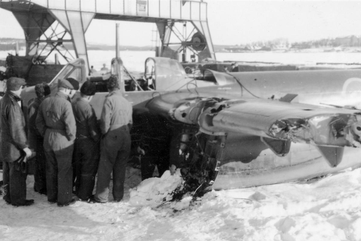 Flygtekniker samlade vid bärgat flygplan B 18 på kajen i Härnösands hamn efter nödlandning på isen den 10 februari 1946. Motorerna har demonterats. I bakgrunden syns en lyftkran som användes vid bärgningen.