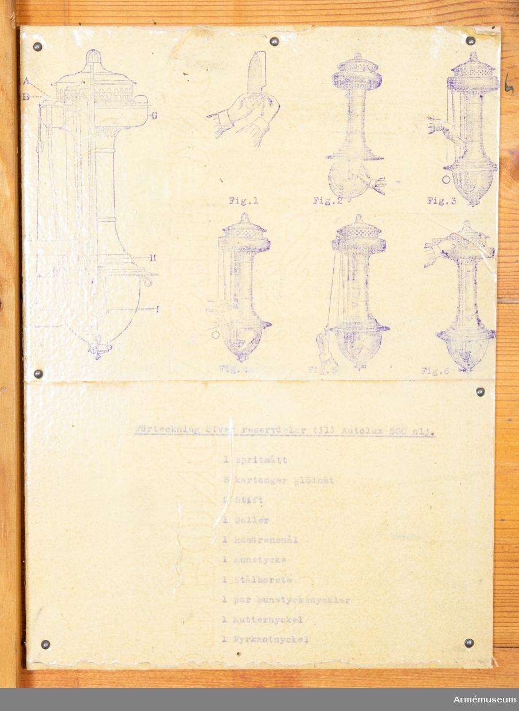 Grupp: I II.     Autoluxlampa, 500 normalljus (nlj), för fältlasarett. Tillverkningsnummer 13113. Kistan innehåller 1 st spritmått, 8 kartonger med glödnät 1 stålborste, 2 stift, 1 galler, 1 handrensnål, 1 munstycke, 1 par munstycksnycklar, 1 mutternyckel, 1 fyrkantsnyckel.