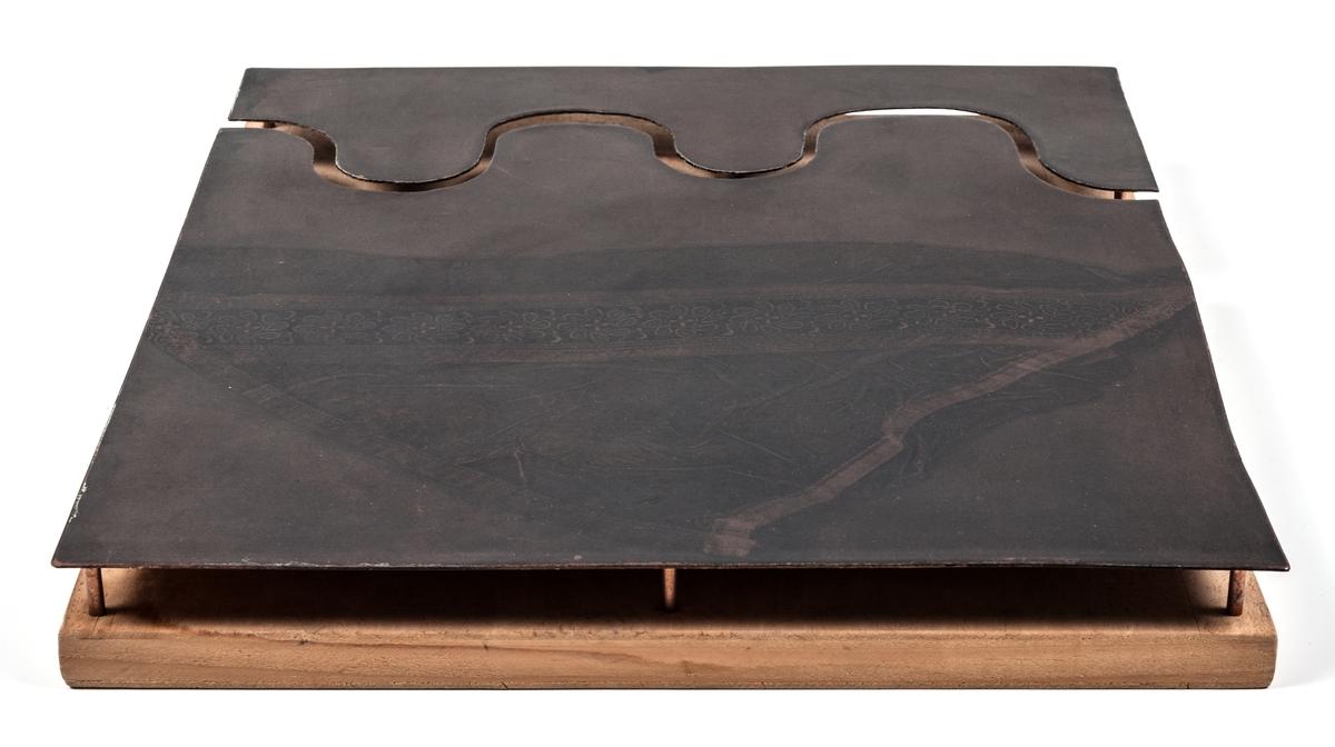 Ett konstobjekt eller montage med en kopparplåt, fäst vid en bakomliggande träskiva för upphängning på vägg. På kopparplåten finns ett motiv tryckt i svart, föreställande en näsduk eller duk. Bilden är inte etsad i plåten utan tryckt på plåten. Ett ovanligt grepp men kan tyckas typiskt för Birger Forsbergs underfundiga humor. GM16221b. är ett grafiskt blad förställande samma motiv som på denna plåt. Osignerad.