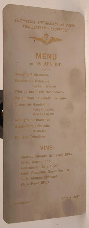 """Mat- och vinlista, etsad på rostfri plåt. 8 maträtter och 6 vinsorter på franska. Text längst upp: """"EUROPEISKA TIDTABELLS- och VAGNKONFERENSEN I STOCKHOLM""""."""