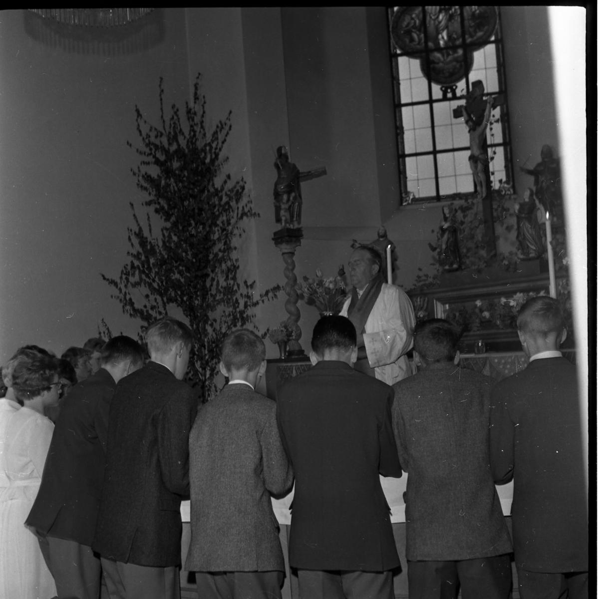 Konfirmander på knä vid altaret framför kyrkoherde Wallis Wendel i Gränna kyrka.